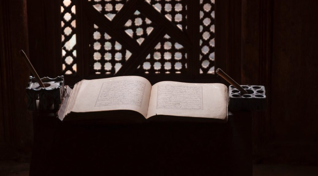 opened koran placed on table in traditional islamic college